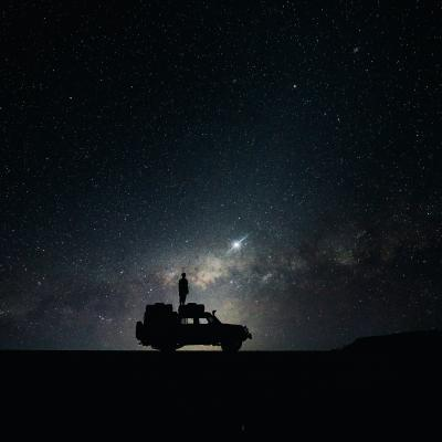 A car silhouetted against the stars