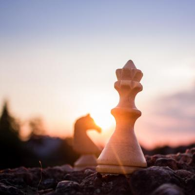 Queen chess piece with sun coming from behind